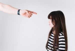 crop-hand-pointing-at-upset-girl_23-2147798382